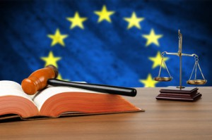 © dekanaryas - Fotolia - Still life photo of a gavel, scales of justice and law book on a judges bench with the European Union flag behind. © dekanaryas - Fotolia